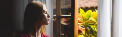 Woman breathing fresh air through a window