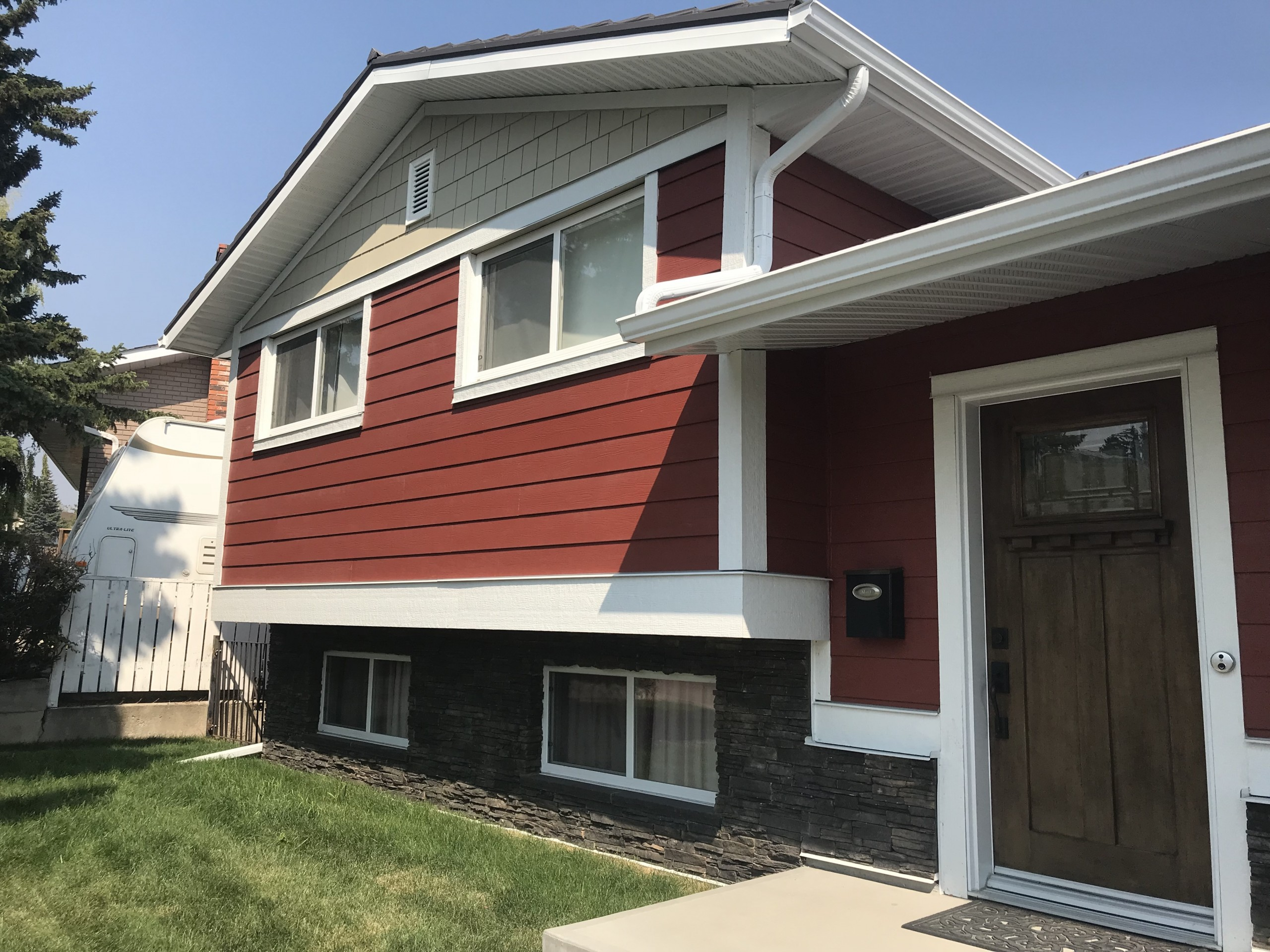 Exterior photo of house renovation showing new red siding, dark stone cladding, light beige shingle siding with white windows and trim.