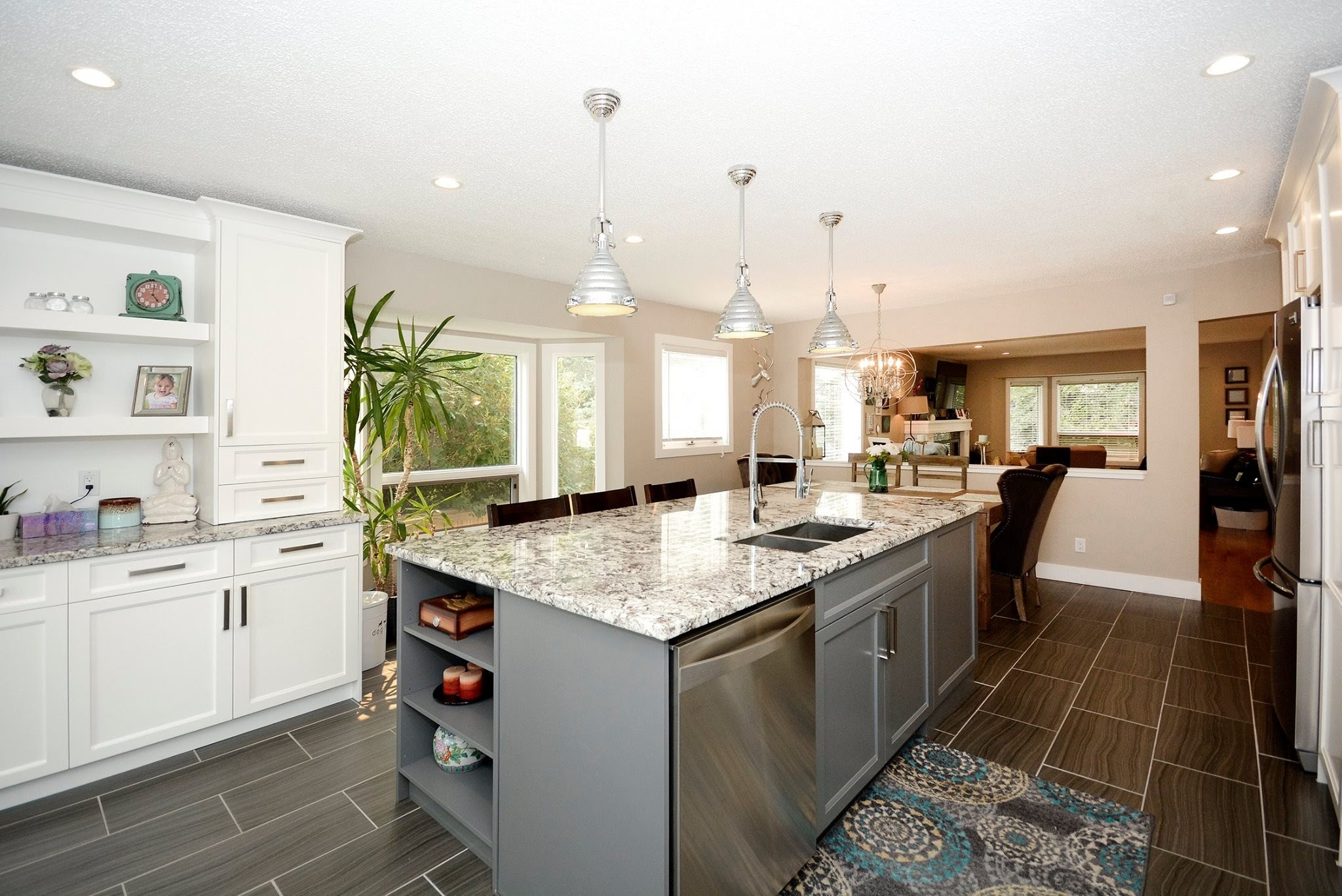 Interior photo of kitchen renovation with new granite-topped work island in the centre, new grey tile flooring with white cabinets and modern light fixtures.