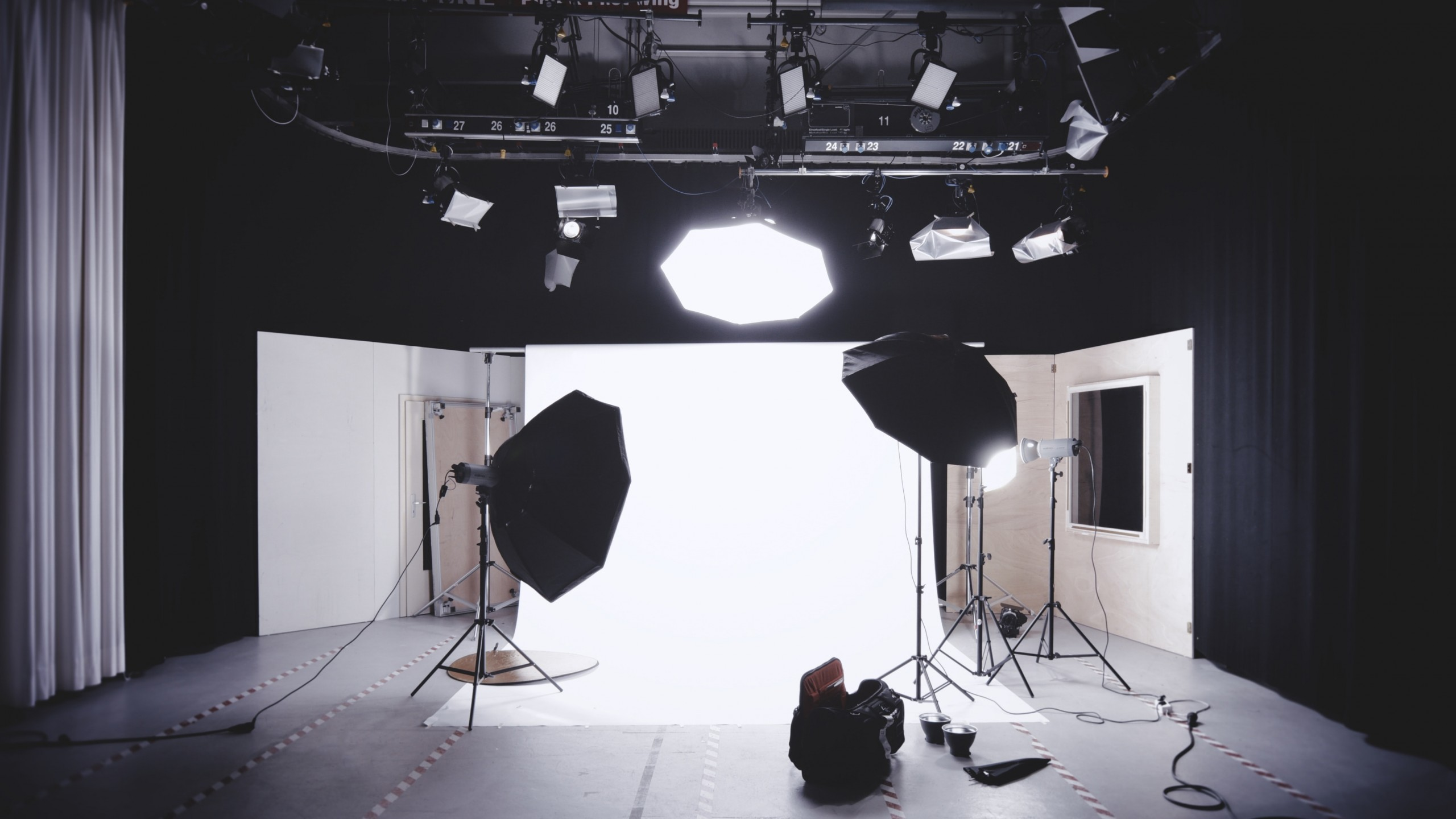Interior photo of theatre space set up as a photo studio with black fabric walls and lighting rigging above.