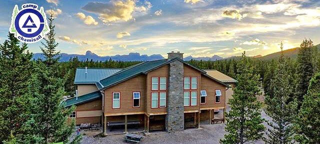 Exterior sunset view of the camp recreation building showing rustic wood and stone cladding to harmonize with the existing camp buildings and the surrounding forest, with a view of the Rocky Mountains in the distance.