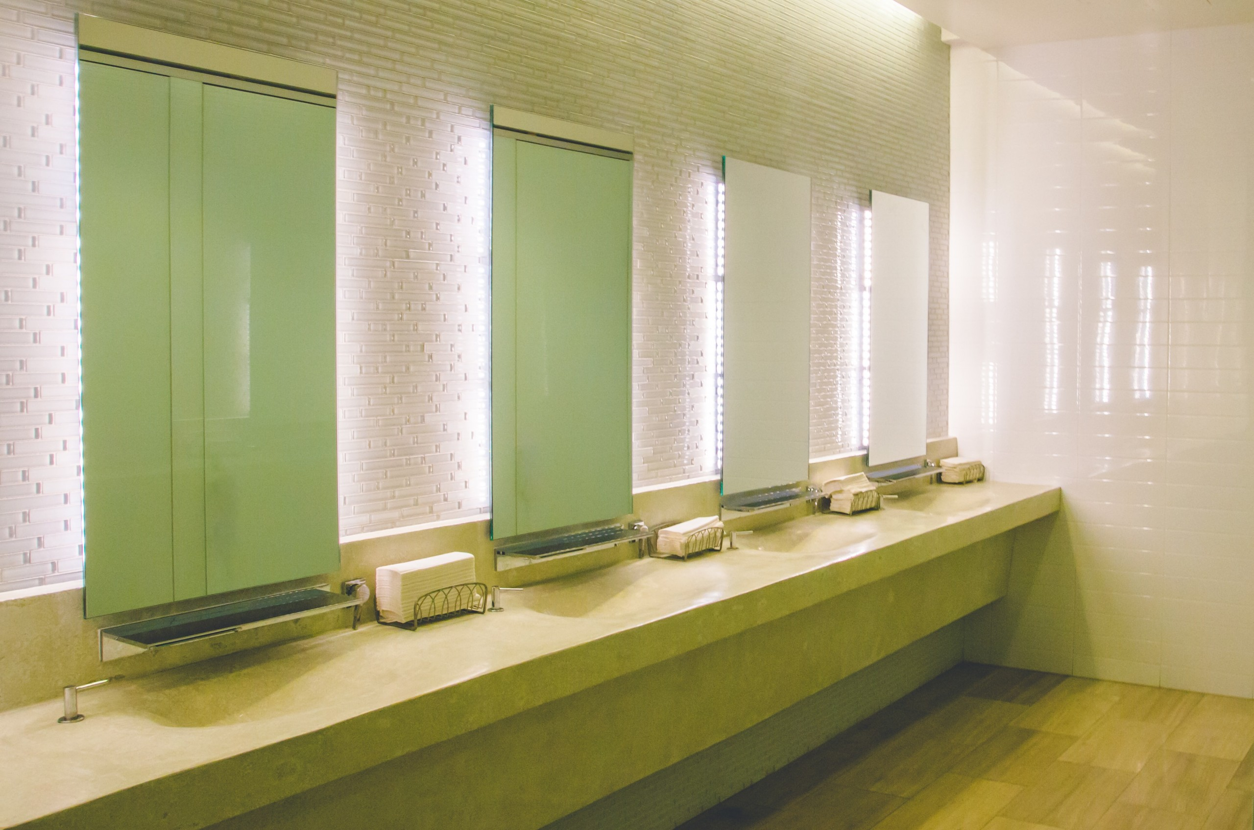 Interior photo of a church washroom showing solid surface countertops, white tile walls and backlit mirrors; light grey neutral colour scheme with tile floor.
