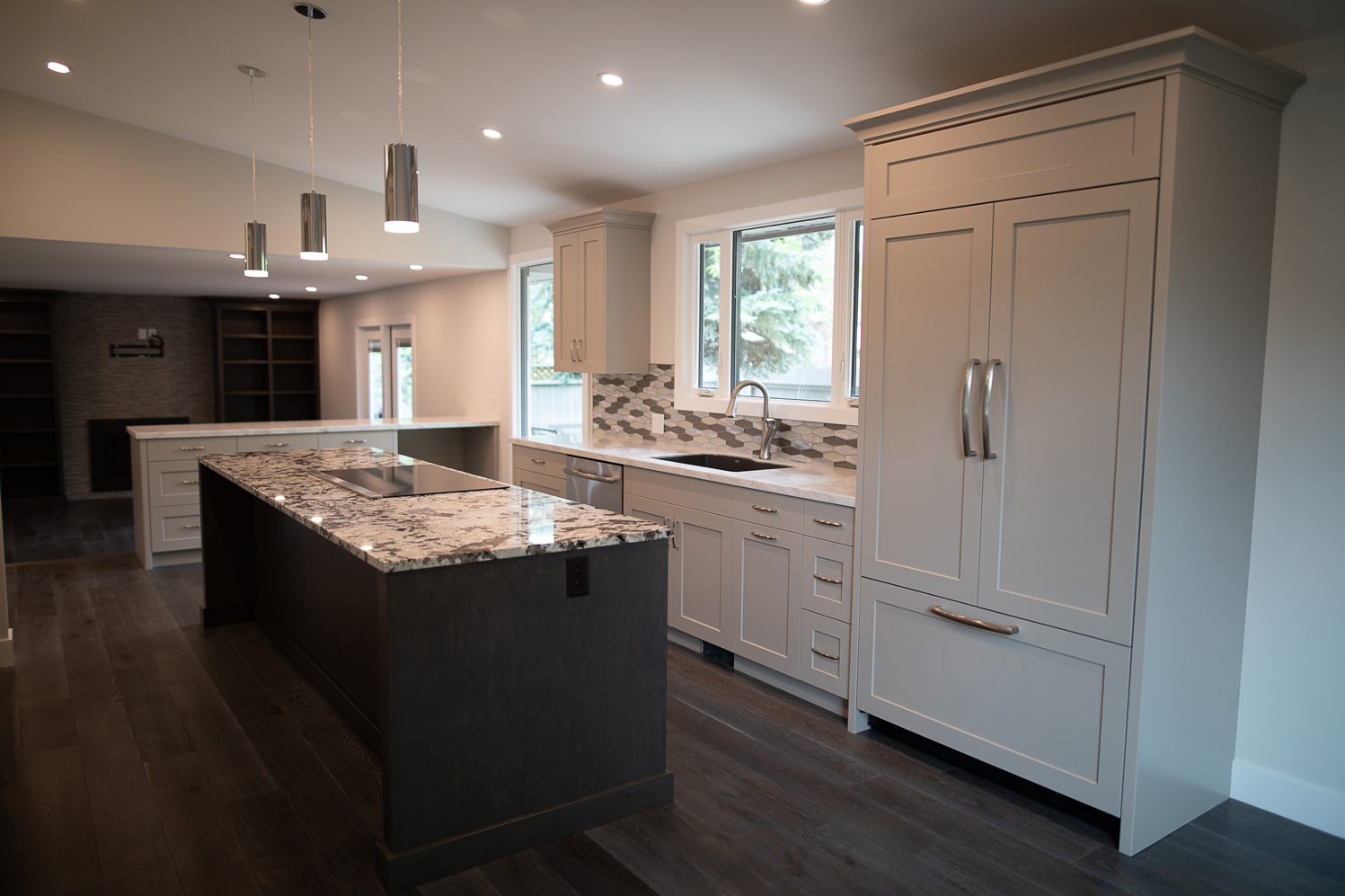 Interior photo of new kitchen showing granite countertops, light grey cabinets, dark wood floors, new vaulted ceiling and modern light fixtures.