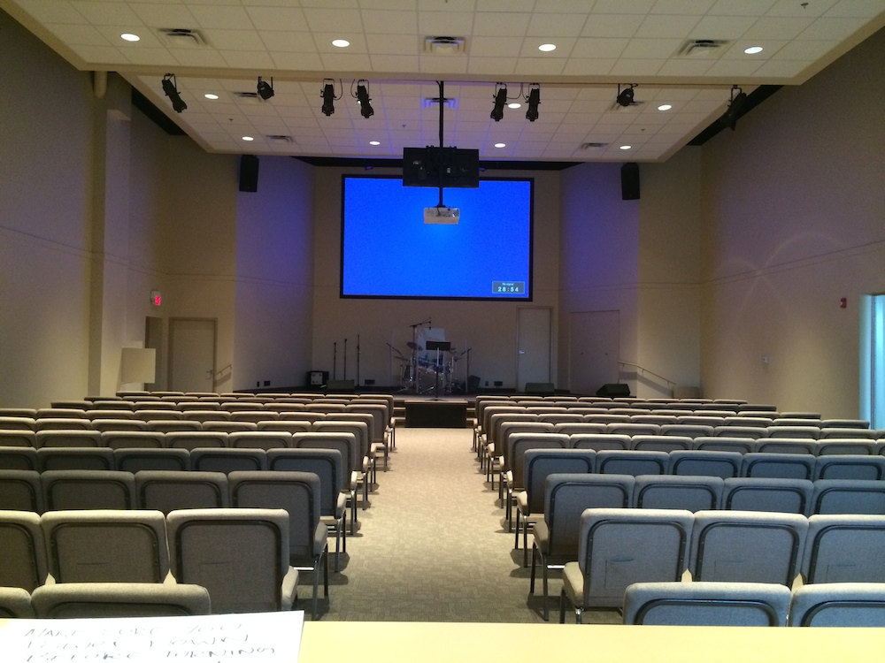Interior photo of renovated chapel, facing the stage; light grey neutral colour scheme, moveable chairs and stage area in front.
