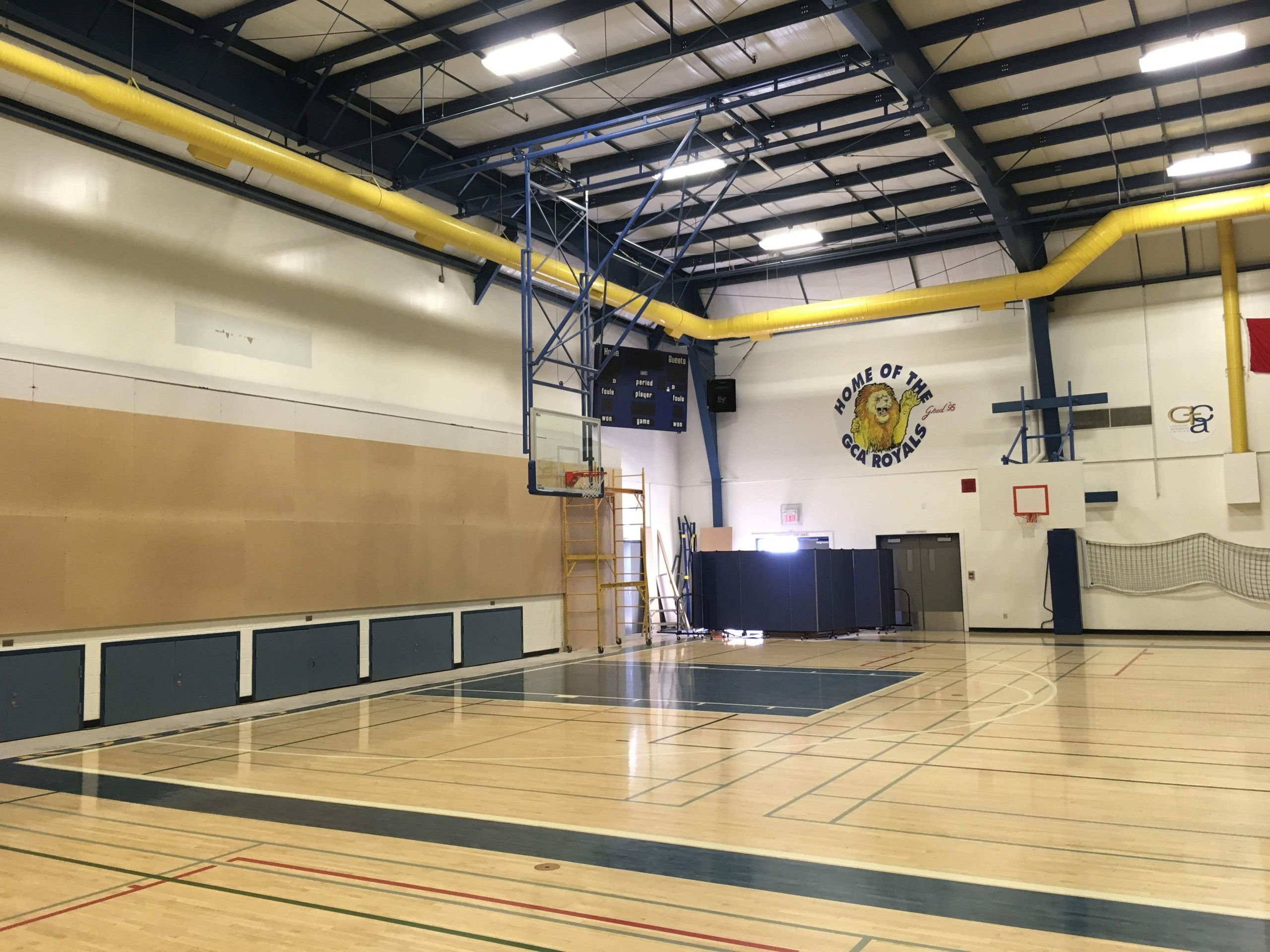 Interior photo of existing gymnasium with enclosed stage area on the left and open steel structure above.