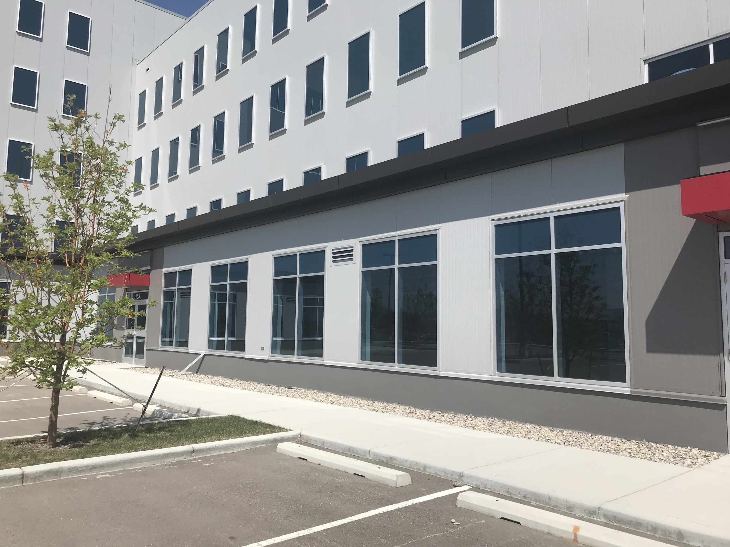 Exterior photo of an existing modern main floor commercial space with grey colour scheme and parking lot in front.