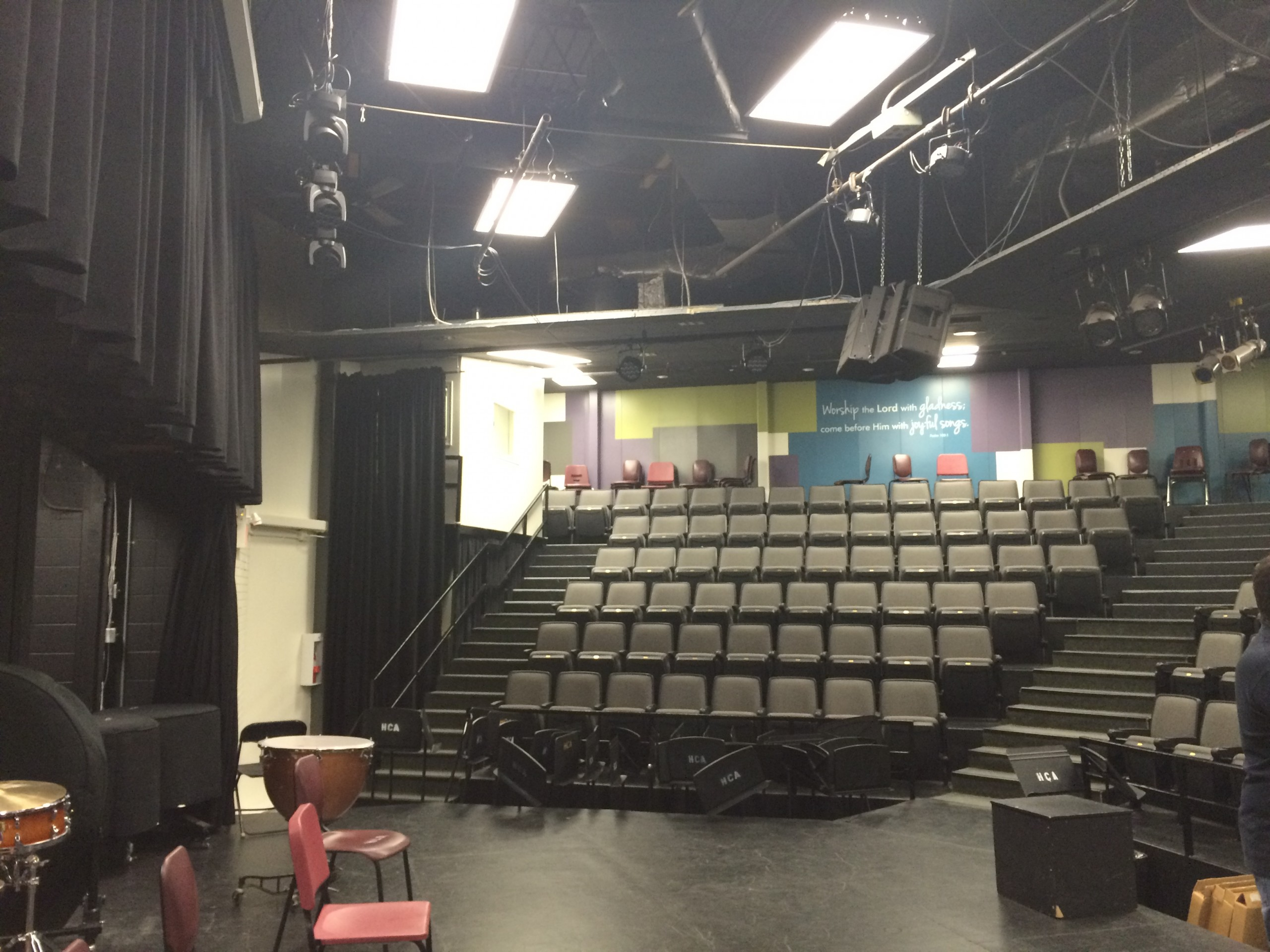 Interior of school theatre room and chapel from the stage, showing risers of seating in the background, lights and sound rigging overhead and colourful accent graphics on back wall.