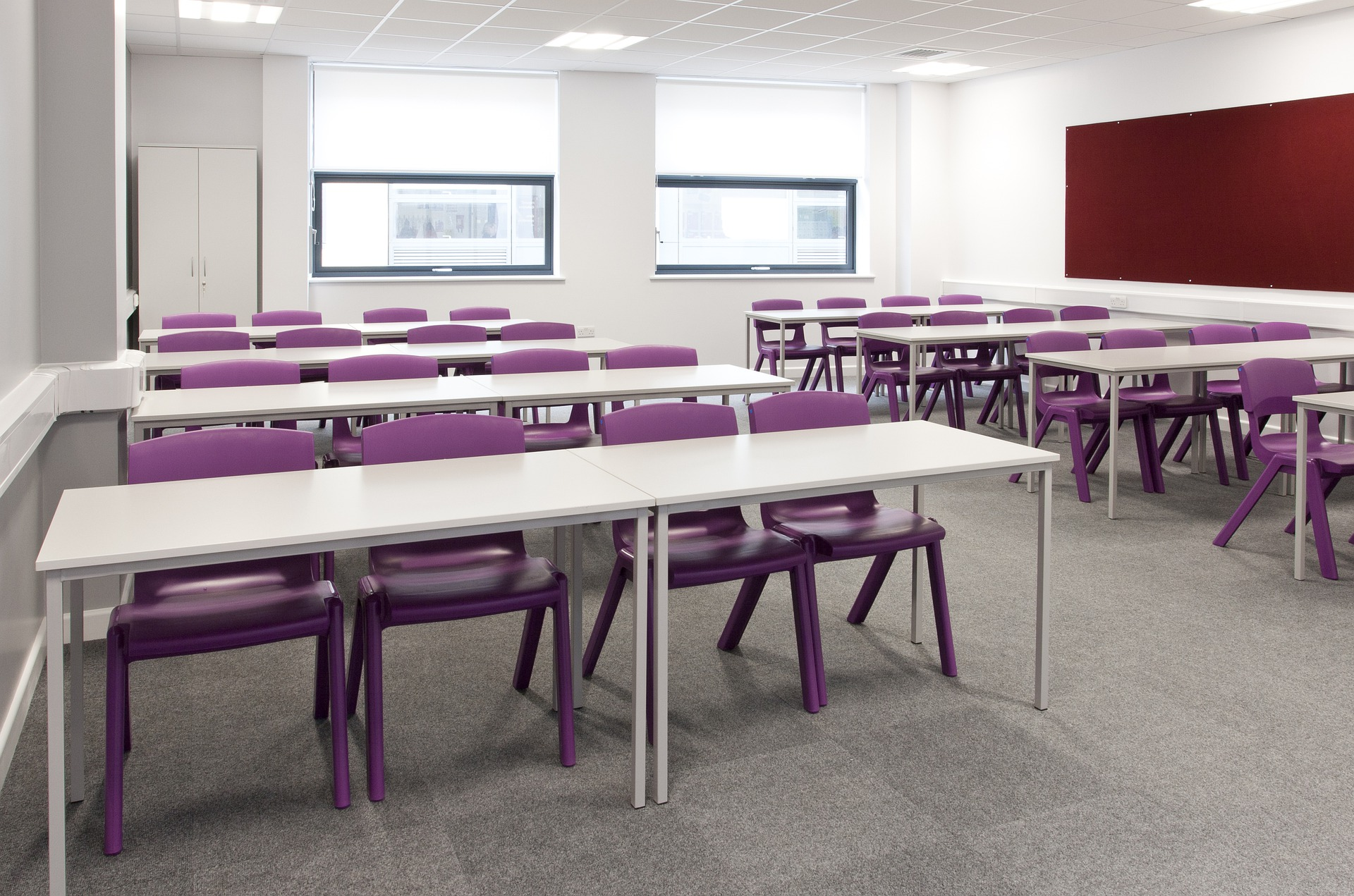 Interior photo of new classroom with neutral white colour scheme and large work desks for students.