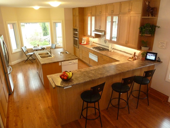 Interior photo of new residential kitchen with bar-height counter in front, large work island in the centre and natural light wood textures throughout.