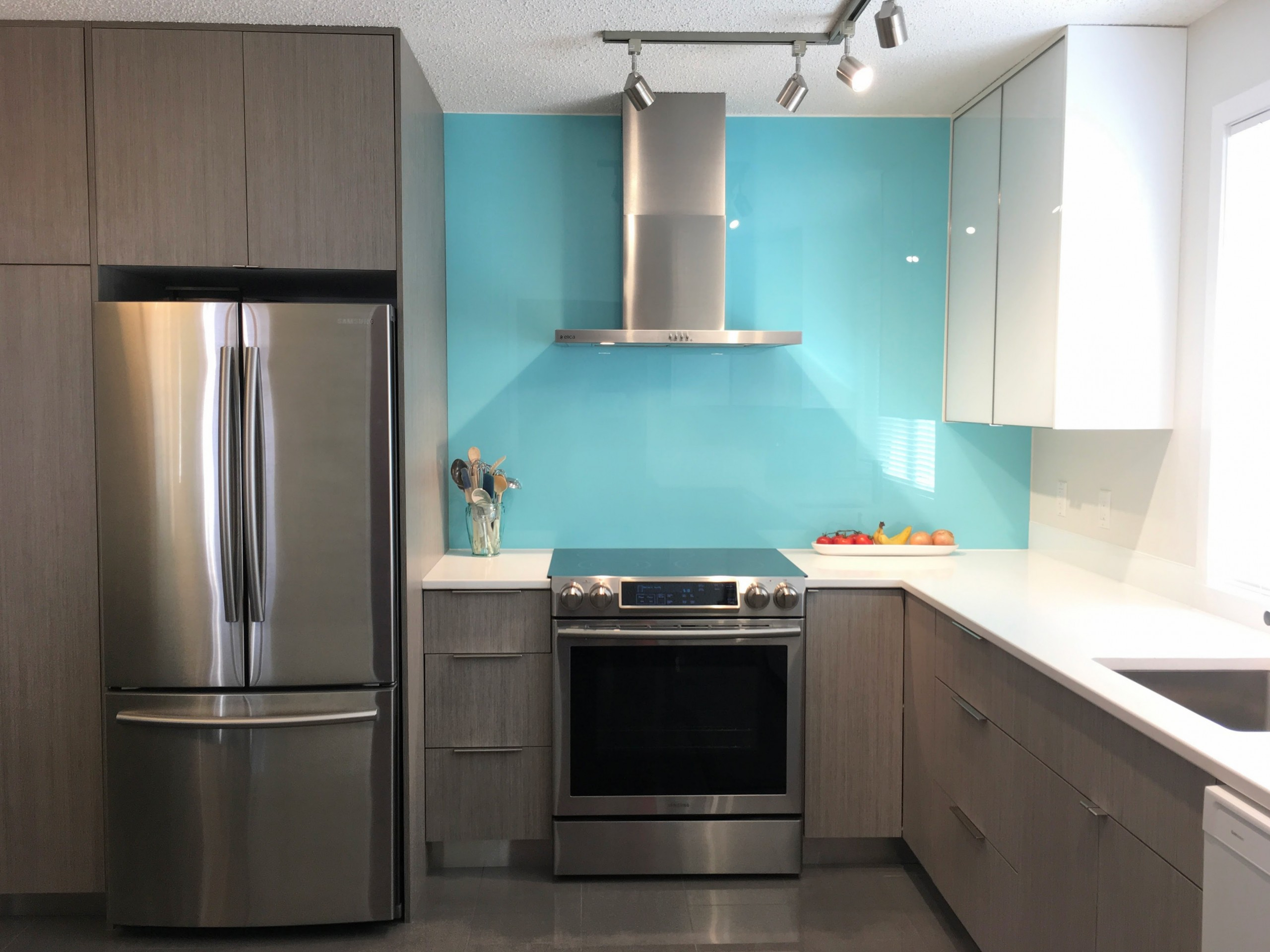Interior photo of grey kitchen cabinets, stainless steel stove and fridge, white quartz counters and teal back-painted tempered glass backsplash.