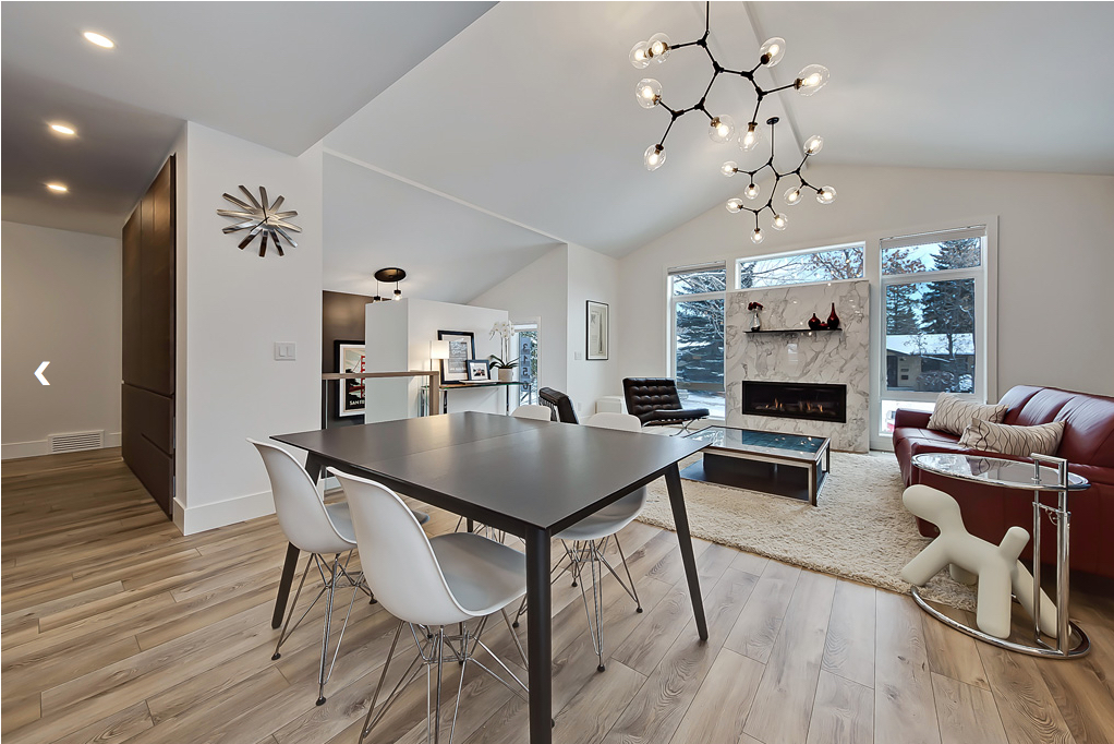 Interior photo of modern house addition showing new vaulted ceiling and gas fireplace surrounded by windows.