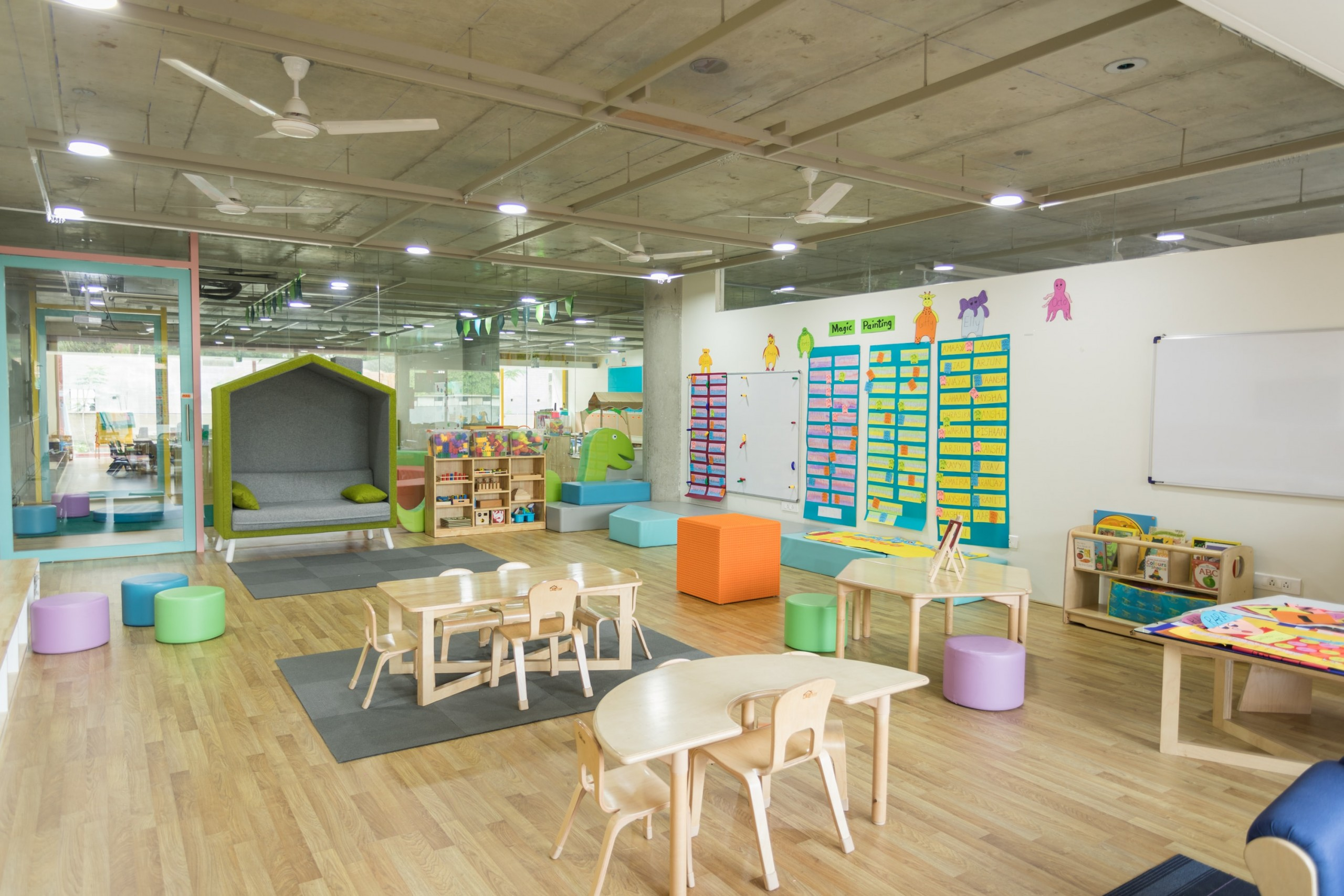 Interior photo showing colourful kids furniture on a wood floor with lots of glass and natural light.