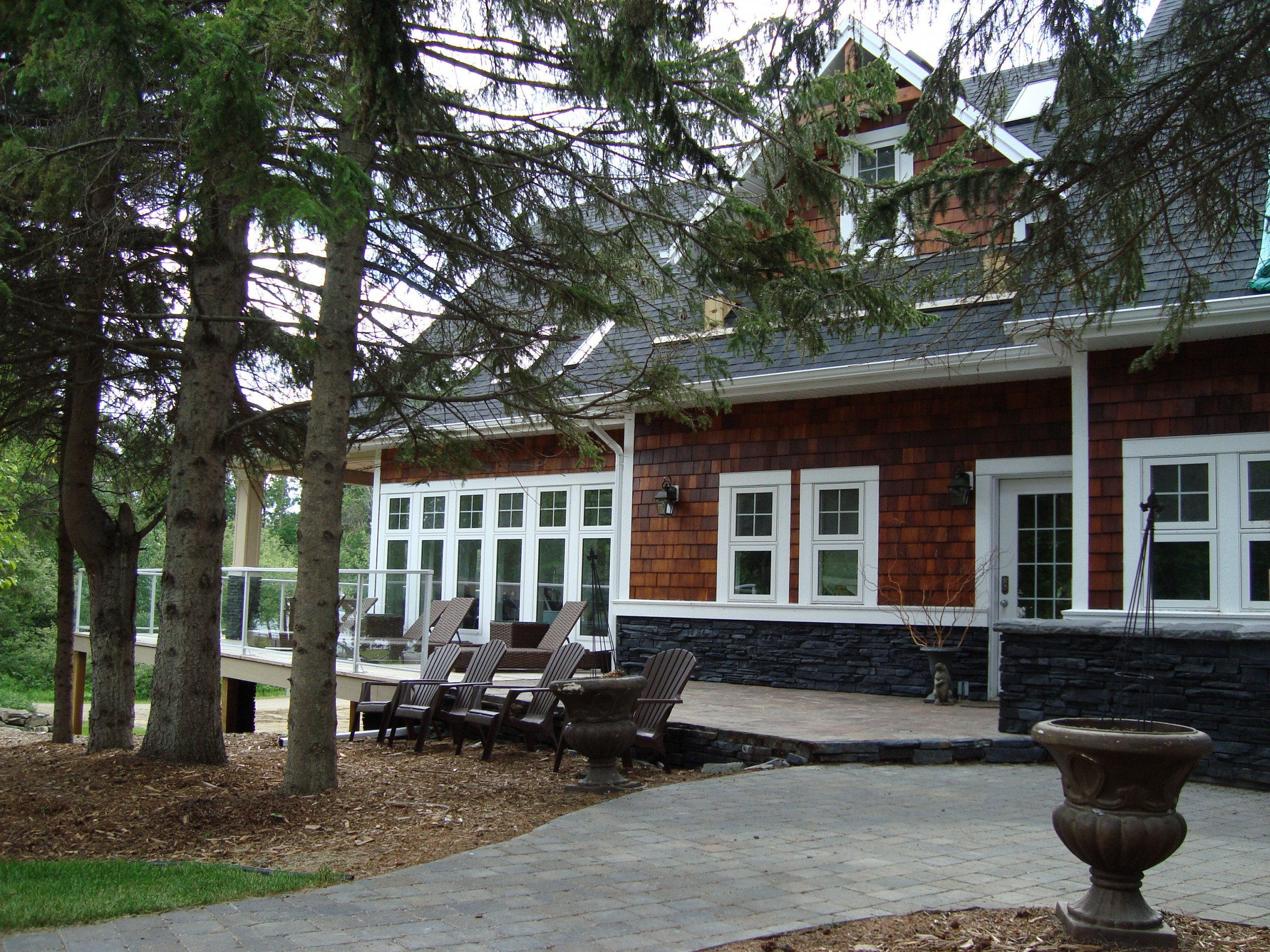 Exterior photo of cabin situated among mature trees, showing brick walkway up to main entrance, clear stained wood shingles and white trim.