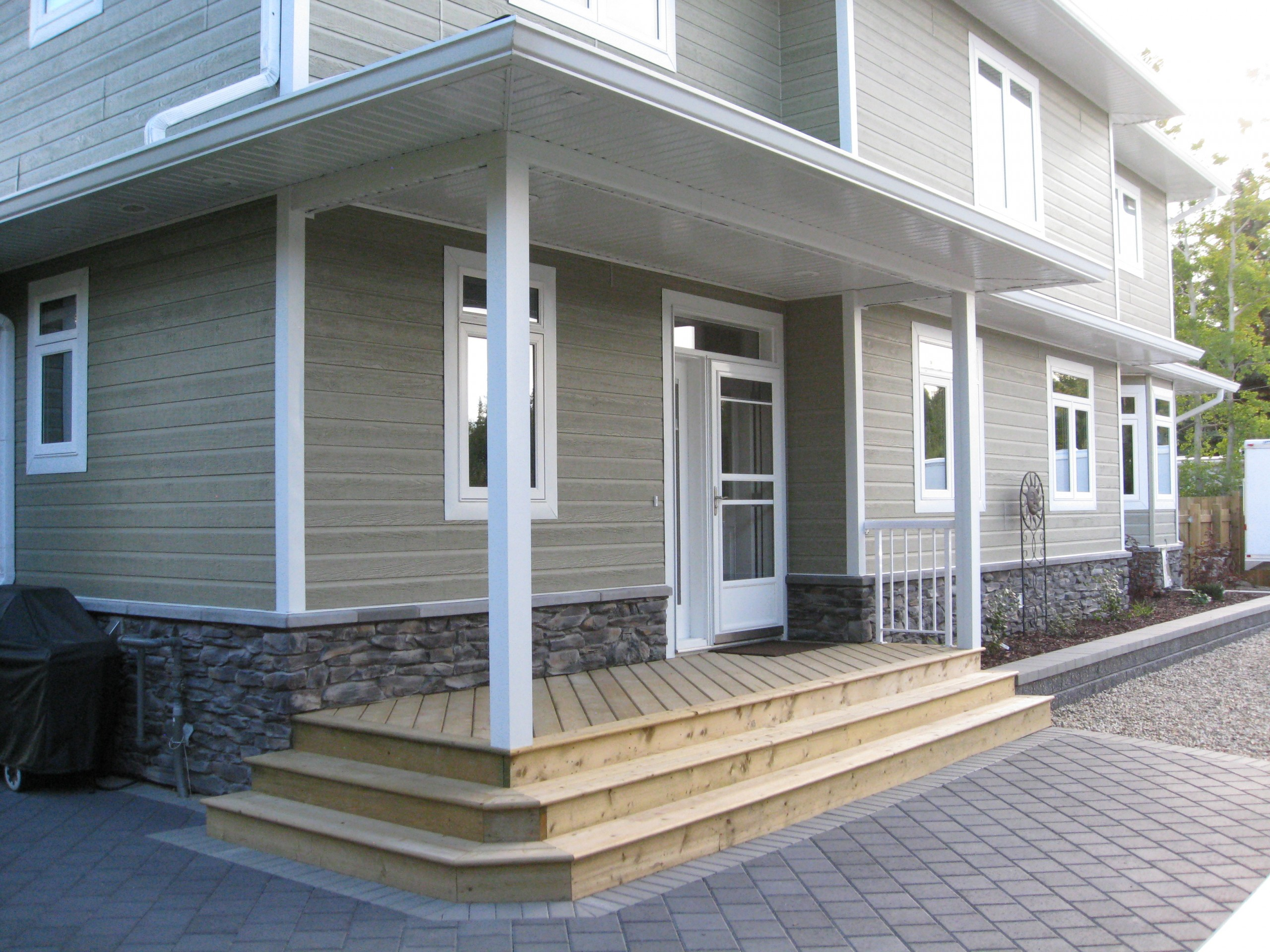 Exterior photo of wooden back porch showing dark stone cladding, medium grey siding and white trim.