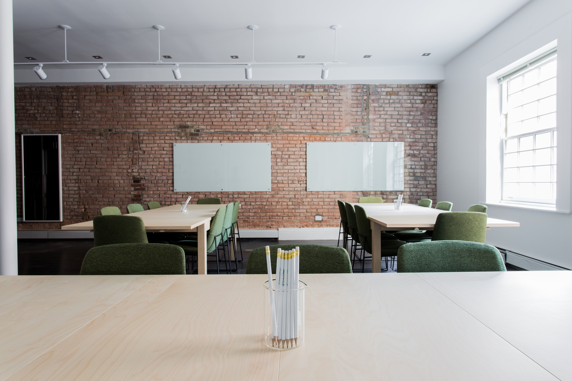 Interior of renovated classroom showing natural brick wall and large window for natural light.