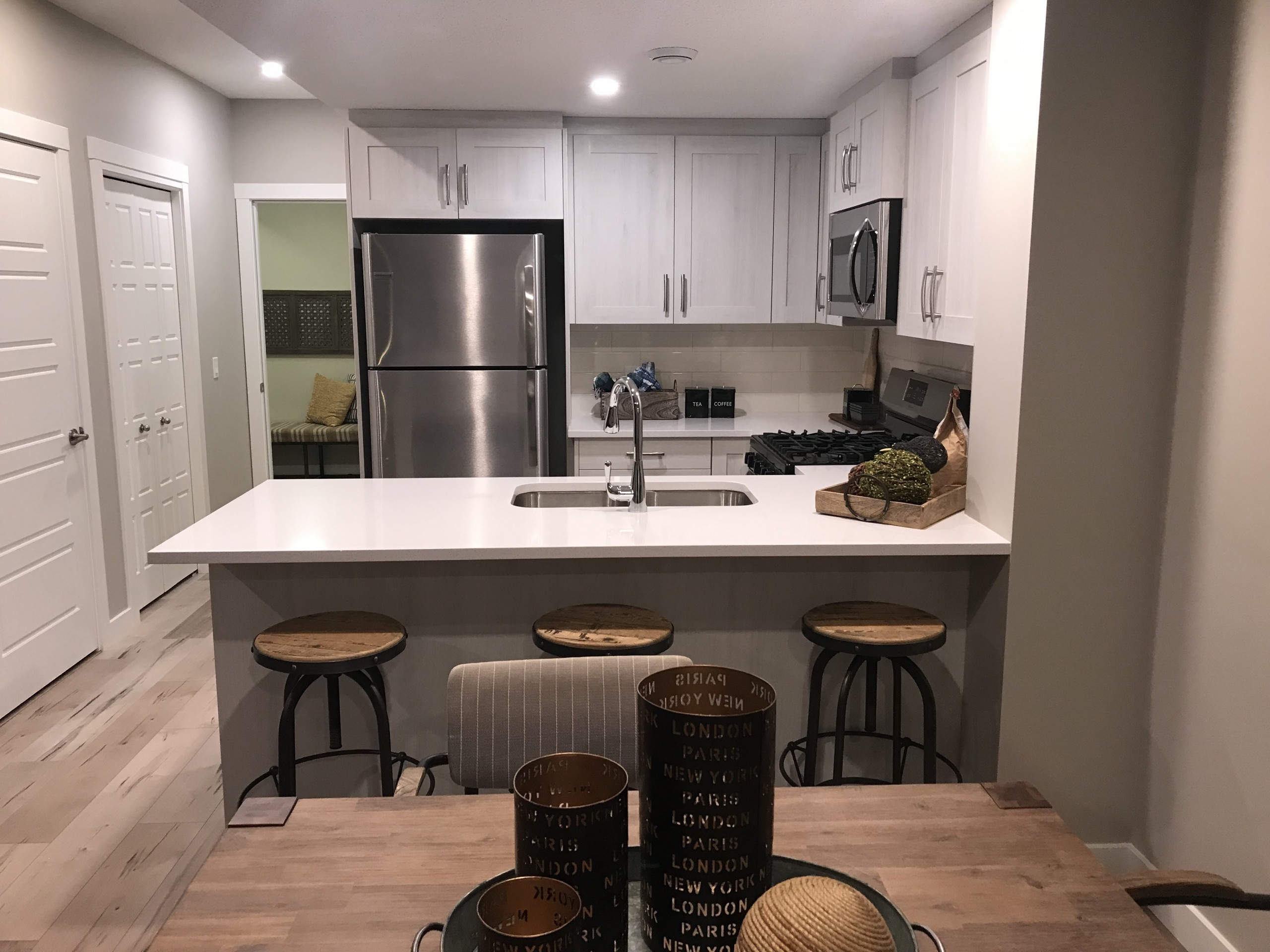 Design of a basement suite showing neutral gray and wood colour scheme with white countertops and accent trim.