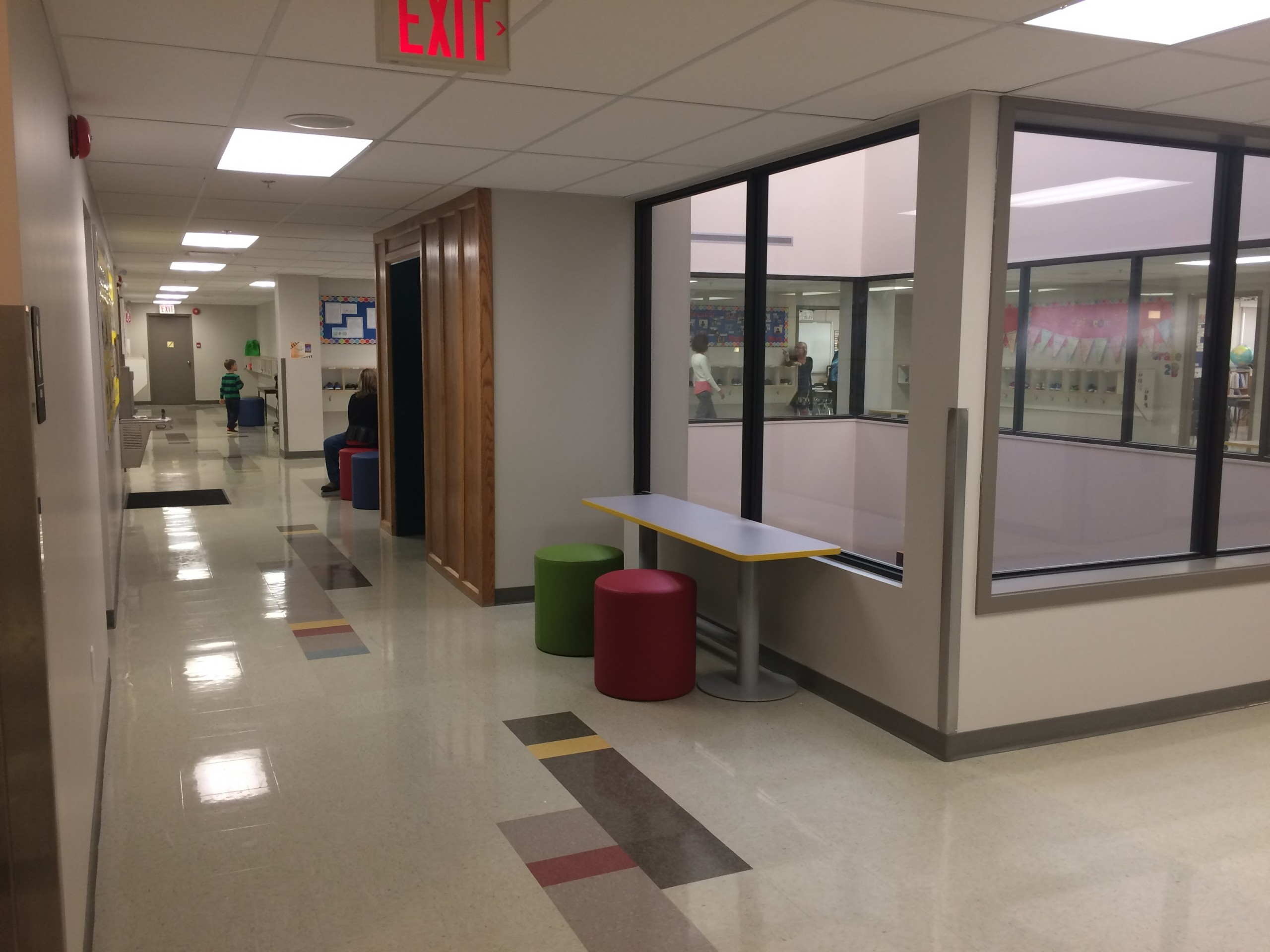 Junior high corridor around a central atrium for improved access to natural light, with colourful furniture and floor patterns.